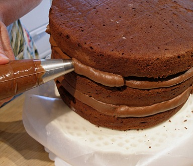 Pipe Or Place Frosting Being Used To Frost The Cake With In Between The Layers To Fill Any Gaps Between The Layers